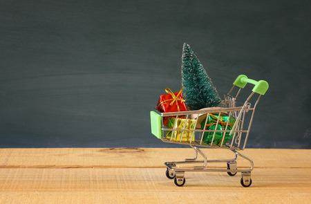 Carro de compras con el árbol de navidad y regalos en la mesa de madera
