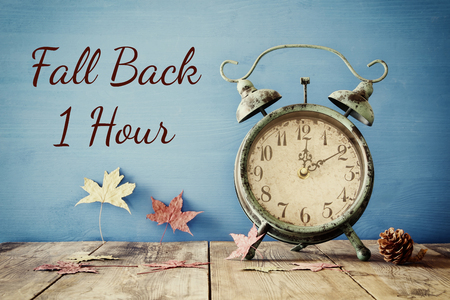 time table: Image of autumn Time Change. Fall back concept. Dry leaves and vintage alarm Clock on  rustic wooden table