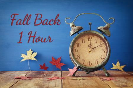 秋時間変更のイメージ。コンセプトにフォールバックします。乾燥した葉と素朴な木製のテーブルにビンテージの目覚まし時計