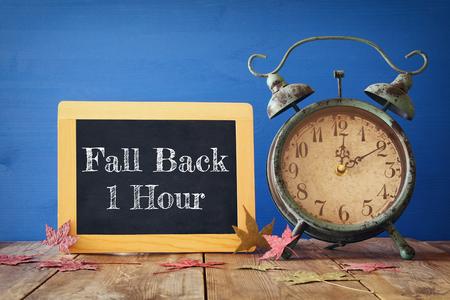 가을 시간 변경의 이미지. 개념을 다시 가을. 마른 나뭇잎과 소박한 나무 테이블에 빈티지 알람 시계 스톡 콘텐츠