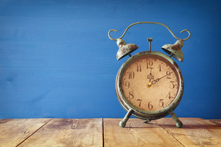 daylight: Image of autumn Time Change. Fall back concept. Dry leaves and vintage alarm Clock on  rustic wooden table