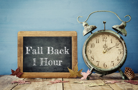 daytime: Image of autumn Time Change. Fall back concept. Dry leaves and vintage alarm Clock on  rustic wooden table
