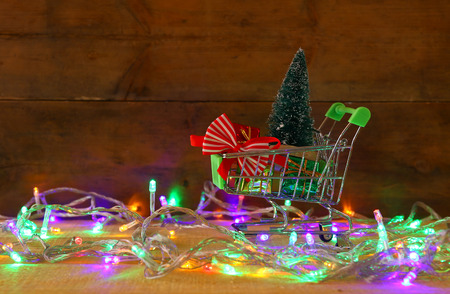 Shopping cart with christmas tree and presents on wooden table with garland colorful lights Foto de archivo