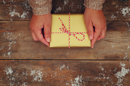 christmas gift box: Woman hands holding Christmas presents on a wooden table.