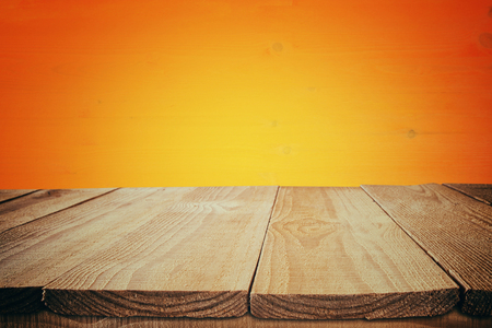 holiday display: Halloween holiday concept. Empty rustic table in front of orange wooden background. Ready for product display montage Stock Photo