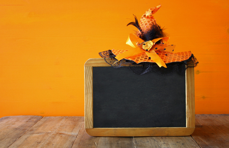 wooden hat: Halloween holiday concept. Cute witch hat next to blank blackboard, on wooden table