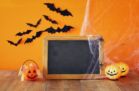 ghost house: Halloween holiday concept. Cute pumpkins next to blank blackboard