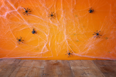 holiday display: Halloween holiday concept. Empty rustic floor in front of spider web background. Ready for product display montage