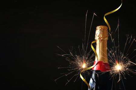 黒い背景の前にシャンパンのボトル。正月やお祝いのコンセプト
