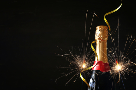 Champagne bottle in front of black background. New year and celebration concept