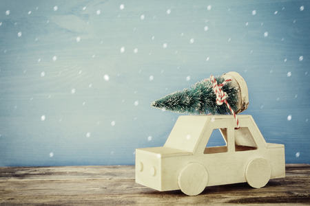christmas toy: Wooden car carrying a christmas tree on the table. Vintage filtered with snow overlay Stock Photo