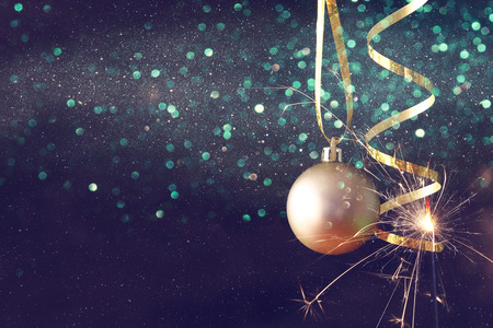 christmas tree ball: Image of christmas festive tree gold ball decoration in front of black background. Glitter overlay Stock Photo