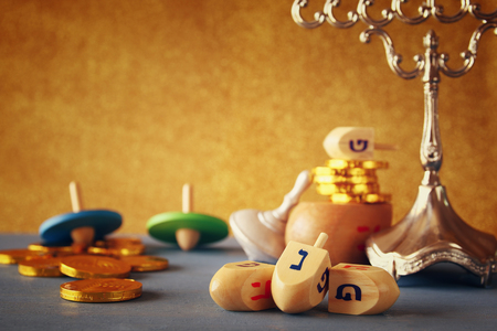 menora: Image of jewish holiday Hanukkah with wooden dreidels colection (spinning top) and chocolate coins on the table