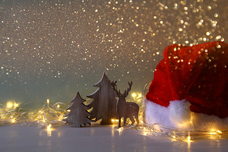 christmas backdrop: Low key Image of wooden christmas tree and deer with garland warm lights next to santa hat