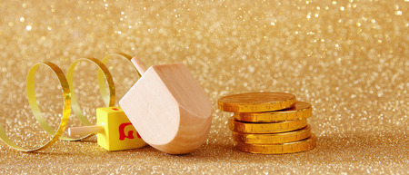 hanukka: Image of jewish holiday Hanukkah with wooden dreidel (spinning top) and chocolate coins on the glitter background. Wide format