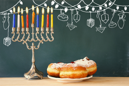 judaica: Image of jewish holiday Hanukkah with menorah (traditional Candelabra) and donuts Stock Photo
