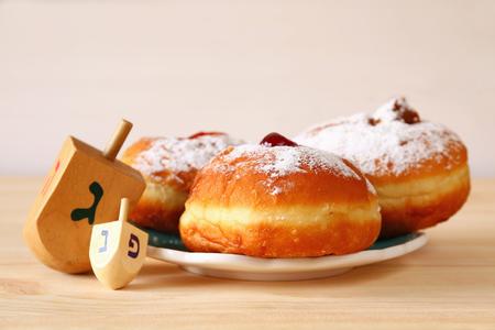 afbeelding van Joodse vakantie Hanukkah met donuts en houten dreidels (tol). retro gefilterd Stockfoto