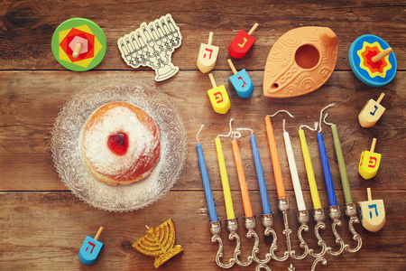 jewish festival: Image of jewish holiday Hanukkah with menorah (traditional Candelabra), donut and wooden dreidel (spinning top)