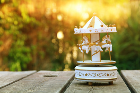 miniature: Vintage white carousel horses over wooden table outdoors in the garden at sunset light