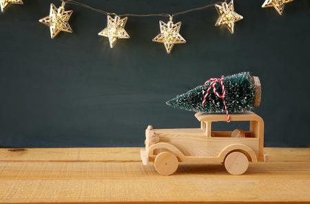 juguetes de madera: Wooden car carrying a christmas tree. Foto de archivo