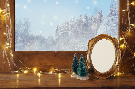 Old window sill with gold christmas lights and empty vintage frame in front of dreamy and magical winter snow landscape background. Ready to put photography Stock Photo