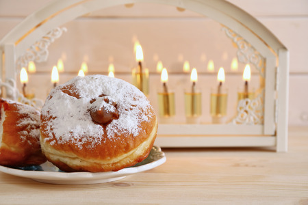 Selective focus image of jewish holiday Hanukkah with menorah (traditional Candelabra) and donuts