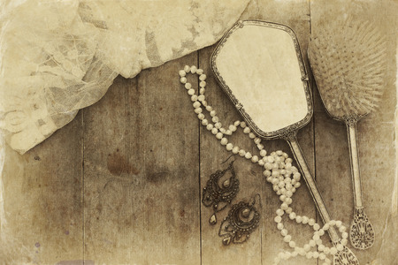 view an elegant wardrobe: Top view image of vintage woman toilet fashion objects on old wooden table. Sepia antique style filtered photo