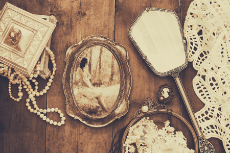 view an elegant wardrobe: Top view image of vintage toilet fashion objects next to photo frame with photography of beautiful woman on old wooden table. Sepia antique style filtered photo