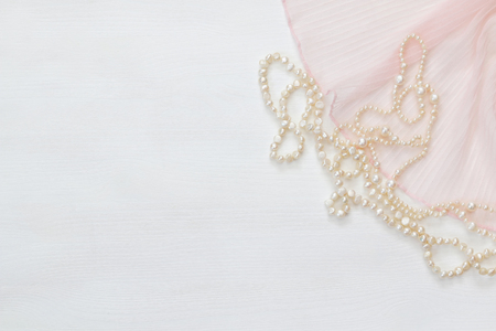 view an elegant wardrobe: Top view image of white pearls necklace.