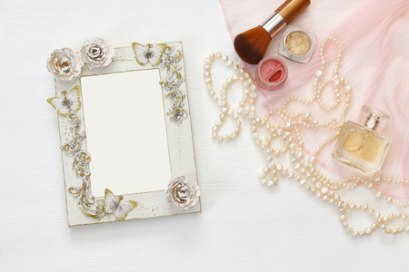 view an elegant wardrobe: Top view image of vintage woman toilet accessory next to blank photo frame on the table