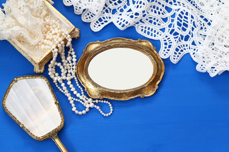 view an elegant wardrobe: Top view image of vintage woman toilet fashion objects next to blank photo frame on old wooden table. Ready for photography montage