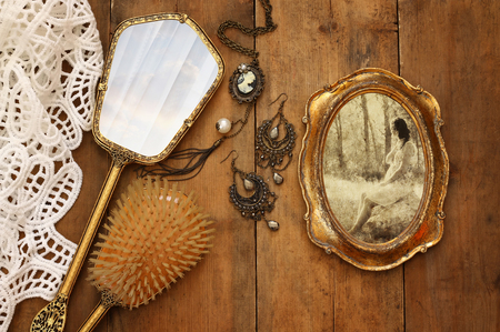 old vintage: Top view image of vintage woman toilet fashion objects next to photo frame with photography of beautiful woman on wooden table Stock Photo