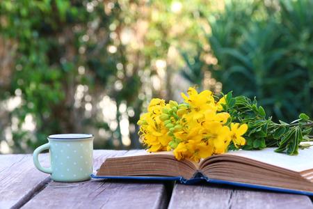 Oud boek, kopje koffie naast veld bloemen op houten tafel buitenshuis in de middag. Selectieve focus Stockfoto