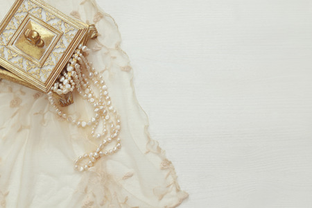 style woman: Top view image of white pearls necklace.