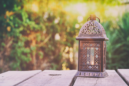 ornamental garden: Vintage oriental lantern over wooden table outdoors in the garden at sunset light. Retro filtered