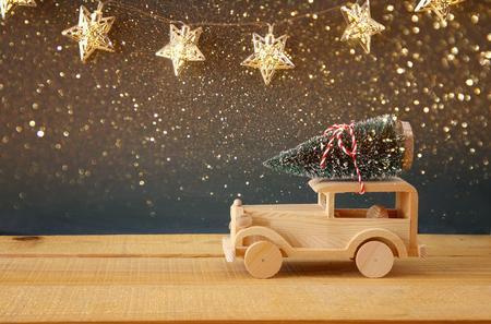 Wooden car carrying a christmas tree. Reklamní fotografie
