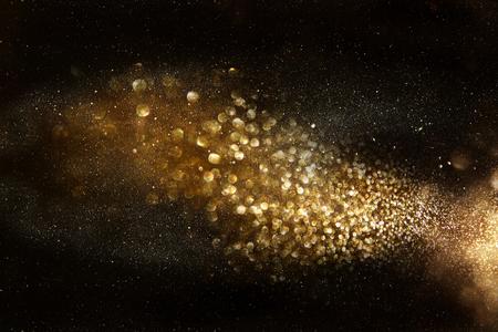 black gold: glitter vintage lights background. dark gold and black. de focused