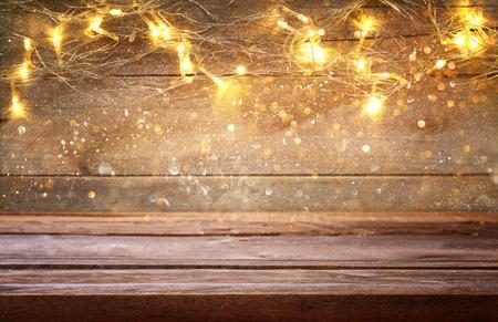 lege tafel voor kerst warme gouden krans lichten op houten rustieke achtergrond. selectieve focus