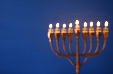 abstract and blurry image of jewish holiday Hanukkah background with menorah (traditional candelabra) and burning candles