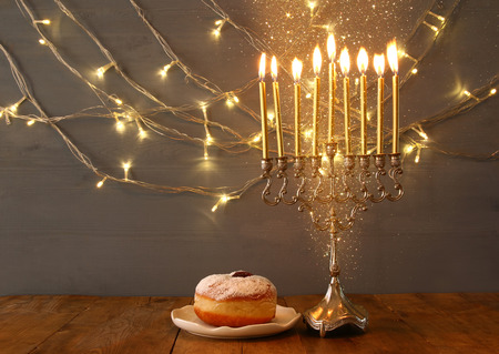 hanukah: Low key Image of jewish holiday Hanukkah with menorah (traditional Candelabra) and donut