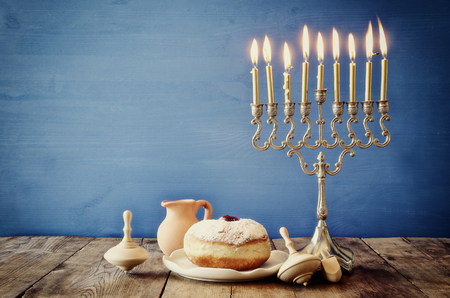 trompo de madera: Image of jewish holiday Hanukkah with menorah (traditional Candelabra), donut and wooden dreidel (spinning top)
