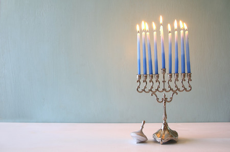 Image of jewish holiday Hanukkah with menorah (traditional Candelabra) and wooden dreidel (spinning top)