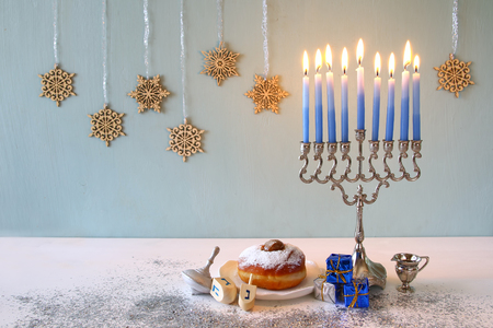 trompo de madera: Image of jewish holiday Hanukkah with menorah (traditional Candelabra) and wooden dreidel (spinning top)