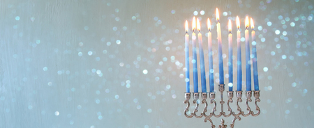 hanukiah: Image of jewish holiday Hanukkah background with menorah (traditional candelabra) and burning candles. Glitter overlay. Wide format