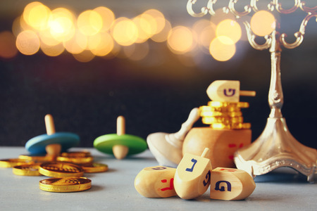 hanukah: Image of jewish holiday Hanukkah with wooden dreidels colection (spinning top) on the table. Glitter overlay