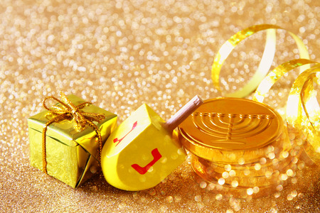 hanukka: Image of jewish holiday Hanukkah with wooden dreidel (spinning top) and chocolate coins on the glitter background Stock Photo