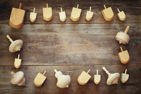 hanukah: Image of jewish holiday Hanukkah with wooden dreidels colection (spinning top) on the table Stock Photo