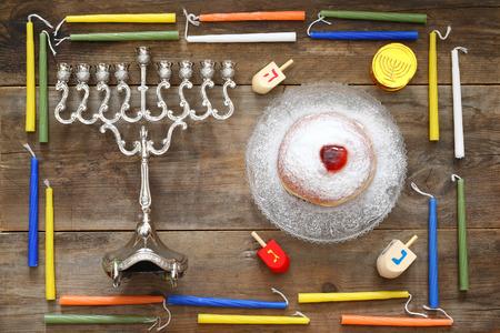 hanukka: Image of jewish holiday Hanukkah with menorah (traditional Candelabra), donut and wooden dreidel (spinning top)