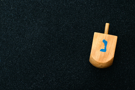 judaica: Image of jewish holiday Hanukkah with wooden dreidel (spinning top) on black glitter background Stock Photo