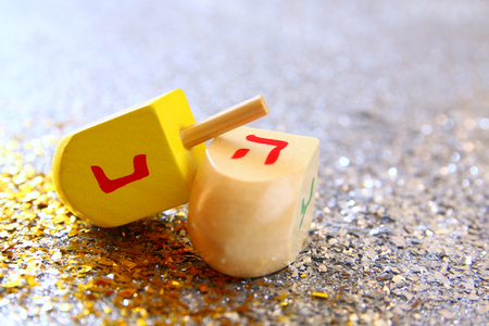 hanukah: Image of jewish holiday Hanukkah with wooden dreidel (spinning top) on the glitter background Stock Photo